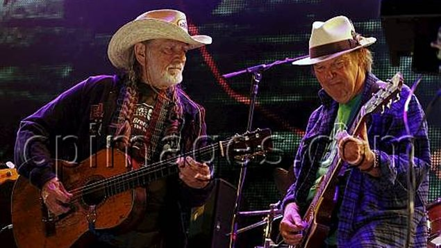 Neil Young, right, and Willie Nelson, seen performing during a 2012 Farm Aid concert, will headline an anti-Keystone XL pipeline concert next month in Nebraska. Willie is wearing a straw cowboy hat and strumming his accoustic guitar and listening as Neil, who is wearing a white fedora with a black band, takes a solo on his electric guitar. Willie is wearing a beat-up sports jacket while Neil has a tatty sweater over a green t-shirt.