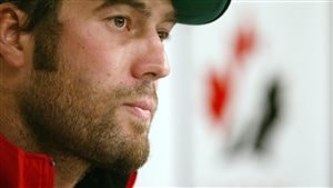 Todd Bertuzzi speaks to the media on the first day of training camp for the Canadian Men's Olympic Hockey Team in Vancouver in 2005. Bertuzzi is shown in right profile from the neck up. He is wearing a baseball cap and has the beginnings of a beard. His eyes are dark and his lips are slightly pursed.