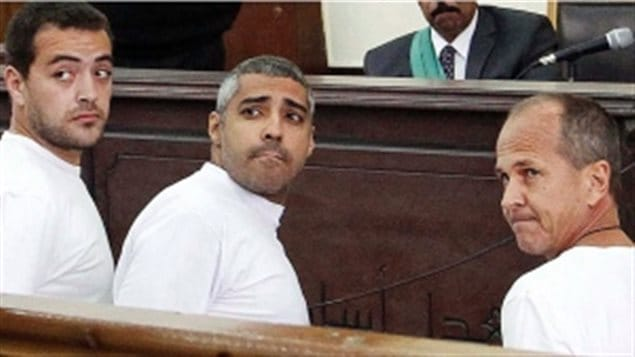 Canadian-Egyptian journalist Mohammed Fahmy, centre, is flanked by Baher Mohamed, left, and Peter Greste, in a Cairo court in March. Mr. Fahmy has short-cropped salt-and-pepper hair and looks a bit like George Clooney. Mr. Mohamed might pass for a professional tennis player and appears athletic. He has short dark hair. Mr. Greste is shorter than the other two and is balding. All are wearing white shirts and looking back toward something that must be happening the court room.