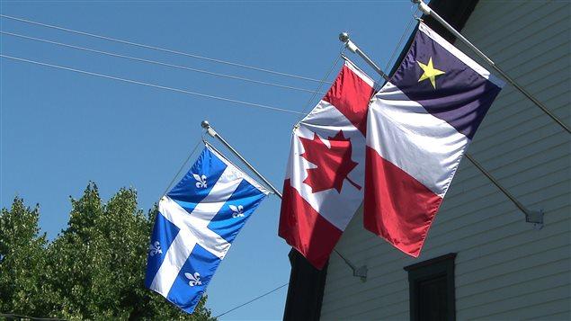 Les drapeaux du Québec, du Canada et le drapeau acadien.