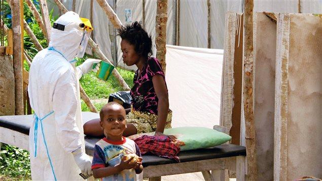 Dans un hôpital gouvernemental du Sierra Leone, un infirmier vêtu d'une combinaison protectrice offre de l'eau à une patiente atteinte de la fièvre d'Ebola.
