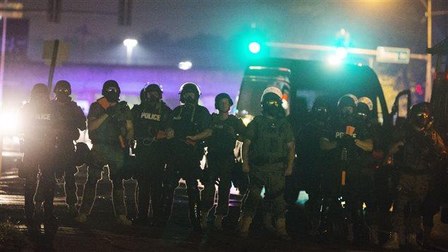 Des policiers munis de masques à gaz se tiennent à distance des manifestants à Ferguson en août dernier.