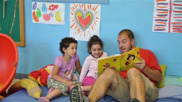 Daniel Laprise, éducateur au CPE Le Bilboquet, raconte une histoire à deux petites filles du CPE.