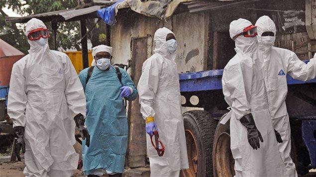 Au Liberia, des travailleurs du réseau de la santé à l'extérieur de la maison d'un homme qui serait mort du virus Ebola.