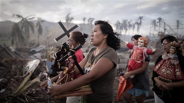 Photo gagnante du World Press Photo dans la catégorie Spots d'information/photo isolée.Dix jours après le passage du typhon Haiyan, des survivants portent des  symboles religieux à Tolosa, sur l'île de Leyte, au centre des Philippines.  Haiyan, l'un des plus puissants typhons jamais enregistrés, a dévasté 47  provinces, causant un énorme ravage, laissant plus d'un million  d'habitations endommagées dont la moitié entièrement détruites, et faisant  plus de 4 millions de déplacés. De vastes zones sont restées sans  électricité ni eau pendant des semaines, et la destruction des  infrastructures a rendu difficiles la distribution de vivres et les soins  médicaux. De nombreux habitants sont partis vers des zones moins  touchées, comme Manille, la capitale, et certaines villes ont vu le nombre  de leurs habitants presque doubler.