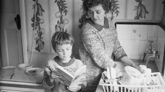 Une mère fait réciter sa leçon à sa fille tout en faisant la vaisselle (mars 1966).