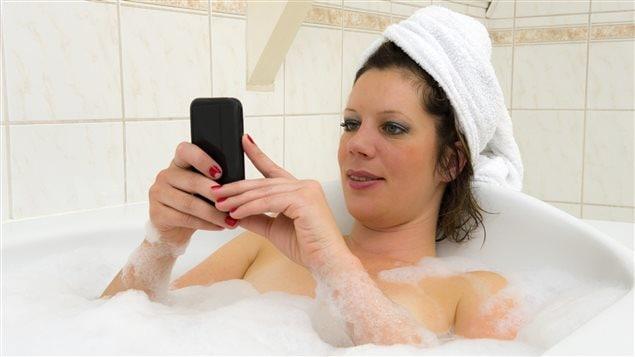Une femme regarde Internet dans son bain.