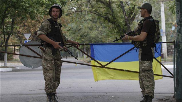 Des soldats montent la garde à Marioupol, dans l'est de l'Ukraine, le 7 septembre 2014.