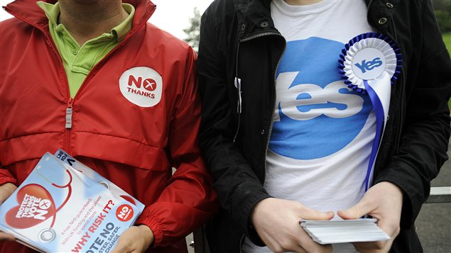 Un partisan unioniste et un partisan indépendantiste à l'entrée d'un bureau de vote à Glasgow, le 18 septembre 2014.