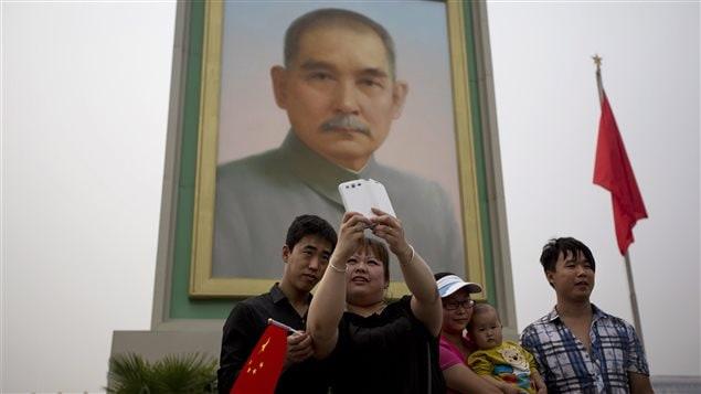 Des Chinois posent devant le portrait de Sun Yat-sen (1er mai 2014)