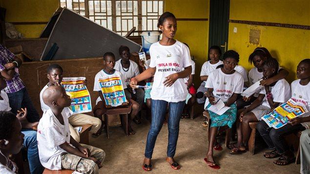 Une travailleuse humanitaire enseigne à prévenir la propagation du virus Ebola et à en reconnaître les symptômes à Freetown, en Sierra Leone.