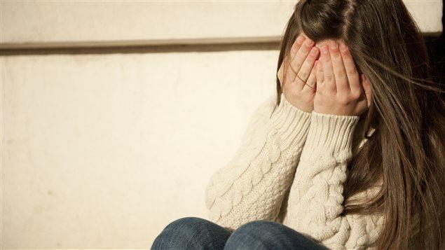 Une fille cache son visage dans ses mains.