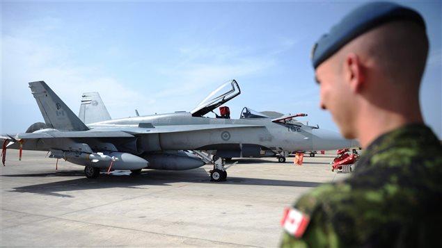 Un soldat canadien observe un CF-18, à Trapani, en Italie.