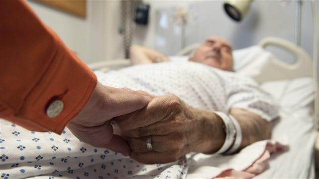 Un vieil homme allongé à l'hôpital tenant la main d'un proche