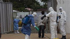 Des travailleurs humanitaires procèdent à la désinfection de leur équipement de protection au Liberia.
