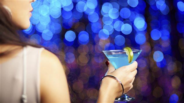 Une femme déguste une boisson alcoolisée.