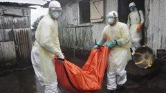 Des travailleurs de la santé emporte le corps d'une femme possiblement morte des suites de l'Ebola.