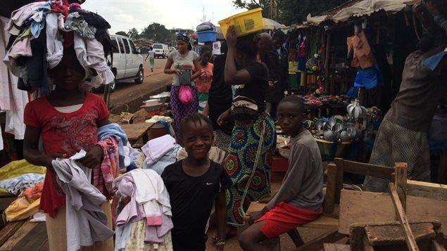 « Petit marché sur la route le Prince à Conakry. La proximité corporelle n'a pas changé. Les enfants sont partout, car les écoles sont fermées pour cause d'Ebola, pour une période indéterminée. »