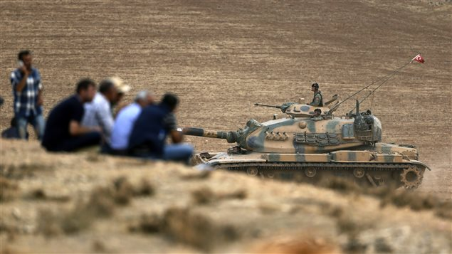 En Turquie, près de la frontière syrienne, un tank de l'armée turque passe près d'un groupe de Kurdes. Ces derniers regardent en direction de Kobané, en Syrie, où leurs compatriotes se battent contre les djihadistes du groupe armé État islamique.