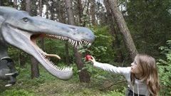 Une jeune fille nourrit un dinosaure