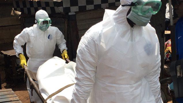 Des travailleurs de la Croix-Rouge guinéenne transportent le corps d'un homme qui pourrait être mort de l'Ebola. Il a agonisé pendant 3 jours sous une étale du marché Madina de Conakry.