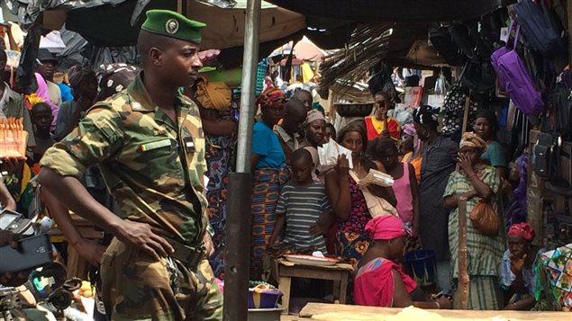 Un soldat et des habitants de Conakry observent l'évacuation  du corps d'un homme qui a agonisé pendant trois jours sous une étale du marché Madina, le plus grand marché du pays.