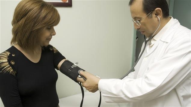 Un médecin vérifie la pression sanguine d'une patiente.