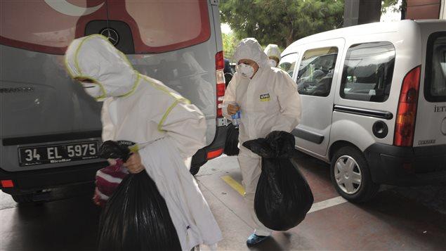 Des membres d'une unité de décontamination turque transportent des sacs contenant des effets provenant du consulat canadien, à Istanbul, le 24 octobre.