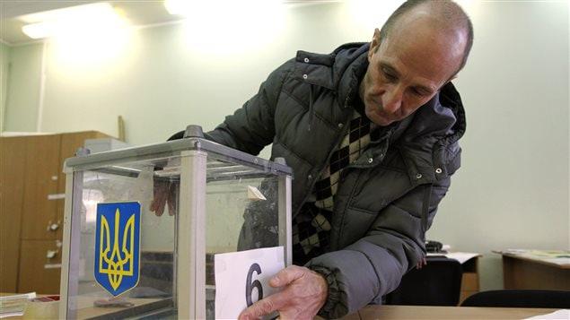 Un travailleur d'élection met la dernière touche aux préparatifs avant le vote de dimanche en Ukraine