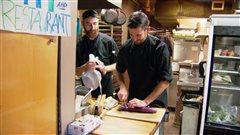 Deux cuisiniers préparent de la nourriture dans un restaurant de Vancouver.