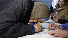Une dame âgée remplit un document avant d'exprimer son droit de vote.