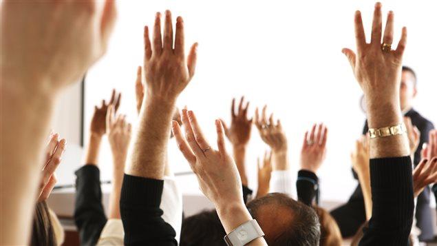 Des personnes lèvent la main pour donner leur opinion.