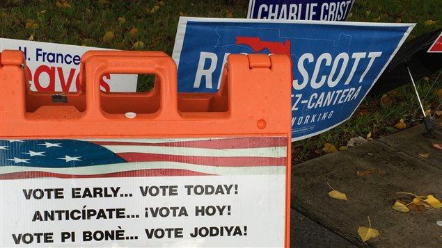 Devant un poste de scrutin par anticipation à Miami. En arrière-plan: les affiches de deux candidats qui se livrent une lutte serrée pour le poste de Gouverneur de la Floride, le républicain sortant Rick Scott et le démocrate Charlie Crist.