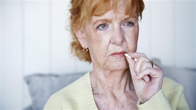 Une femme âgée prend une pilule pour soulager sa douleur.