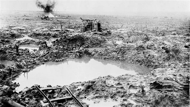 Brtish tank, mired and hit in the mud of Passchendaele 1917, the remains of a light rail track in the forefront and what appears to be an artillery piece in the background where a shell has just exploded. In these conditions, Canadians prevailed