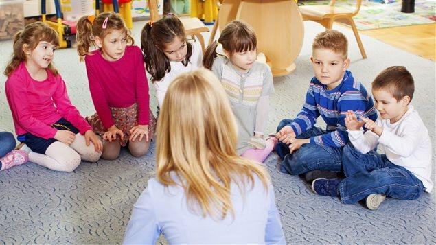 Une enseignante parle à des enfants.
