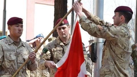 Des soldats baissent le drapeau canadien pour la dernière fois en Afghanistan, le 12 mars 2014, après une mission 12 ans.