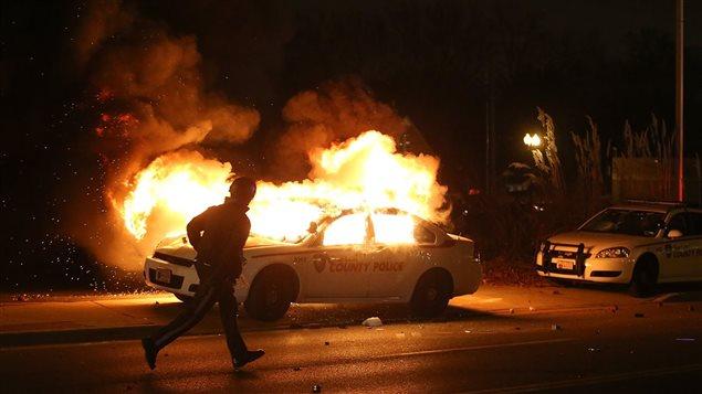 Une voiture de police incendiée lors de la manifestation qui a suivi l'annonce du grand jury à Ferguson.