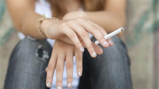 Une adolescente fume une cigarette.