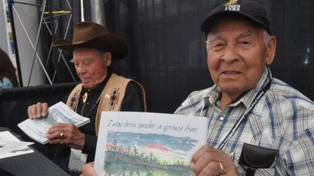 Alex Van Bibber (g) et son frère Pat Van Bibber avec en main des exemplaires du livre I was born under a spruce tree de leur frère JJ Van Bibber en juillet 2013.