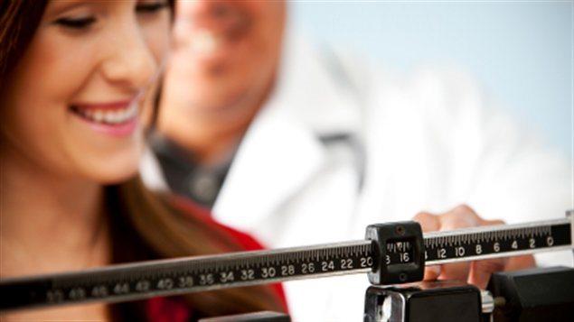 Une dame sur un pèse-personne chez son médecin