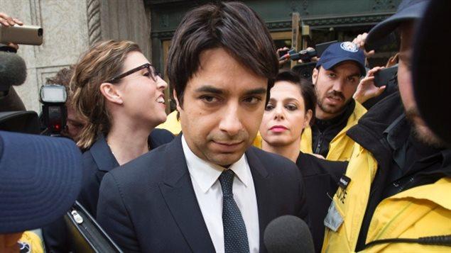 L'ancien animateur radio de CBC, Jian Gomeshi, est escorté par la police à la sortie du palais de justice, le 26 novembre.