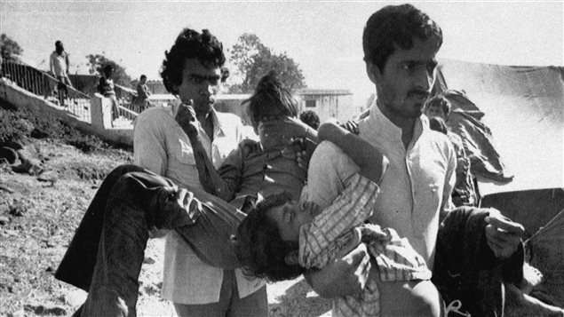 Deux hommes transportent à l'hôpital des enfants aveuglés par la catastrophe survenue à Bhopal, en décembre 1984.