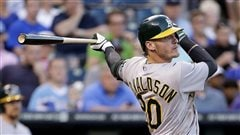 The Jays are hoping Josh Donaldson can provide some pop at the plate and steady defence at third base this season. We see Donaldson completing his backswing after a hit in an green and grey Oakland uniform. His black bat held in his back (left) hand is extended behind him.