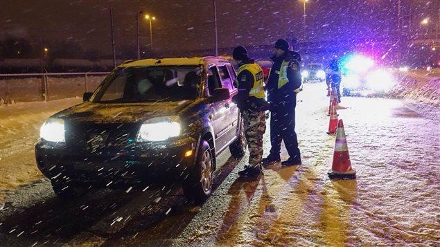 Des policiers arrêtent les véhicules pour vérifier l'état des conducteurs.