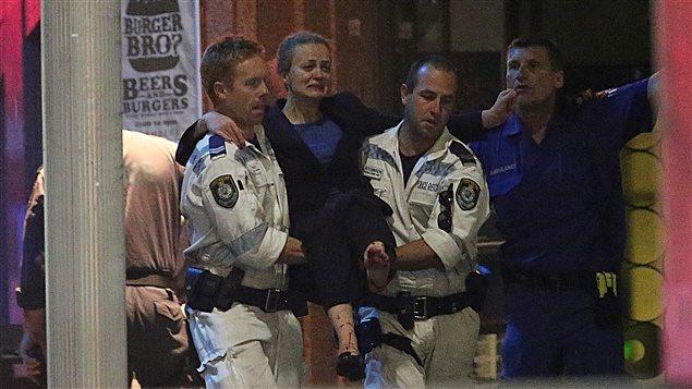 La police australienne évacue des otages lors de l'assaut final.