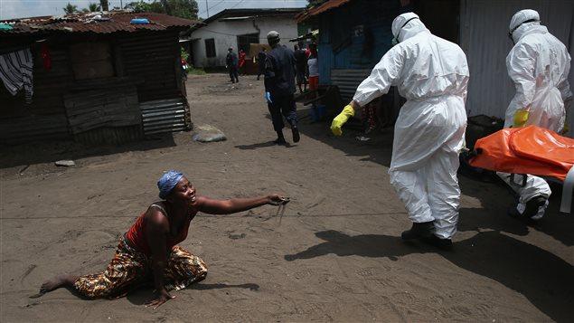Una mujer postrada ofrece un puñado de tierra al cuerpo de su hermana fallecida a causa del Ébola y que está a punto de ser cremada. Monrovia, Liberia, 10 de octubre de 2014.