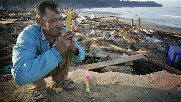 Un homme prie pour sa soeur disparue dans le tsunami de 2004 en Thaïlande