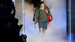 Milos Raonic arrives to play Roger Federer in their ATP World Tour Finals tennis match at the O2 Arena in London in November. Raonic appeared over matched, but continues move up the rankings. We see Raonic with his red equipment bag slung over his left shoulder wearing a brown warm-up jacket and dark blue pants. He is emerging from a tunnel surrounded by dry ice steam.