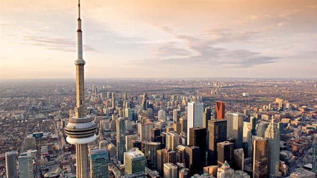 Toronto's CN Tower and the Financial District, where CEOs are seeing their compensation soar, compared to other Canadians. In this aerial shot from the west, we see the CN Tower in the foreground and the skyscrapers of the financial district bound together reaching skyward.